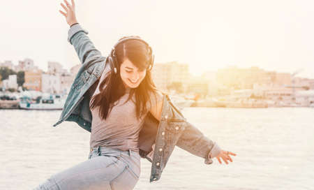 Photo for Young girl listen to music with headphones - Woman has fun dancing outdoors with the sea on the background - warm contrast filter - Royalty Free Image