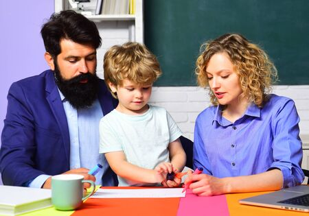 Foto de Home family schooling. Parents teaching kids private lessons in math. Back to school. Home schooling. Mathematics for kids. Pupil learning letters and numbers with parents. Parents helps child boy - Imagen libre de derechos
