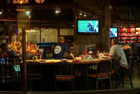 Photo pour Uncasville, CT USA. Restaurant and bar patrons watching the big football game as viewed through glass. - image libre de droit