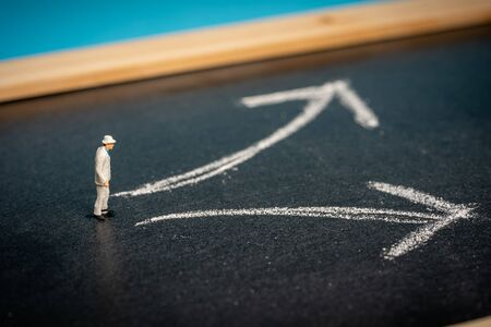 Photo pour Business concept: Decision making. Miniature man on chalkboard with two arrows pointing at different directions - image libre de droit