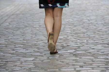 Shot of woman legs walking on cobbled pavement.