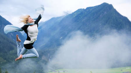 Young beautiful woman jumping at mountain