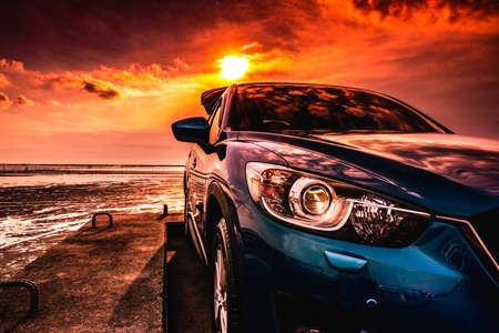 Photo pour Blue compact SUV car with sport, modern, and luxury design parked on concrete road by the sea at sunset. Front view of beautiful hybrid car. Driving with confidence. Travel on vacation at the beach. - image libre de droit