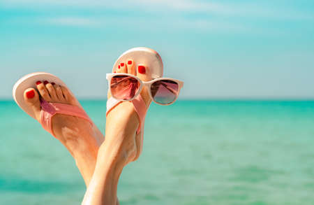 Foto de Upside woman feet and red pedicure wearing pink sandals, sunglasses at seaside. Funny and happy fashion young woman relax on vacation. Chill out girl at beach. Creative for tour agent. Weekend travel. - Imagen libre de derechos