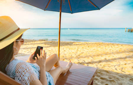 Photo pour Asian woman with hat sit on sunbed under beach umbrella at sand beach and using smartphone on summer vacation. Girl in casual style relax and enjoy holiday at tropical paradise beach. Summer vibes. - image libre de droit