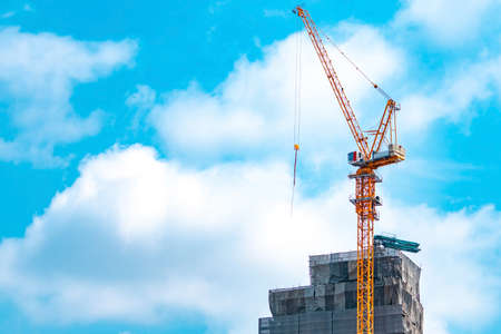 Photo for Construction site with crane and building. Real estate industry. Crane use reel lift up equipment in construction site. Building made of steel and concrete. Crane work against blue sky and white cloud - Royalty Free Image