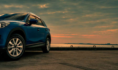 Photo for Blue compact SUV car with sport and modern design parked on concrete road by the sea at sunset in the evening. Hybrid and electric car technology concept. Car parking space. Automotive industry. - Royalty Free Image