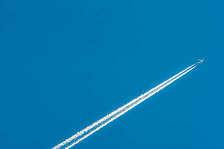 Photo pour Airplane with white condensation tracks. Jet plane on clear blue sky with vapor trail. Travel by aeroplane concept. Trails of exhaust gas from airplane engine. Aircraft with white stripes. - image libre de droit