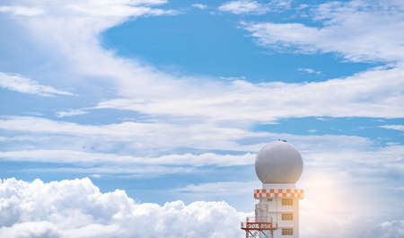 Weather observations radar dome station against blue sky and white fluffy clouds. Aeronautical meteorological observations station tower use for safety aircraft in aviation business. Spherical tower.