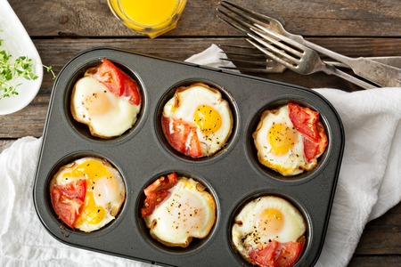 Photo pour Baked eggs with ham and tomato in maffin tin - image libre de droit