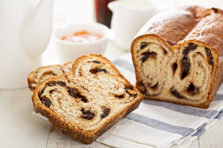 Cinnamon raisin bread for breakfast on white table with coffee