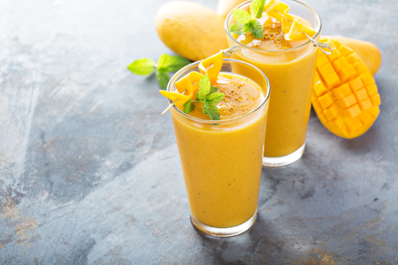 Refreshing and healthy mango smoothie in tall glasses