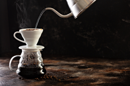 Foto de Making pour over coffee with hot water being poured from a kettle - Imagen libre de derechos