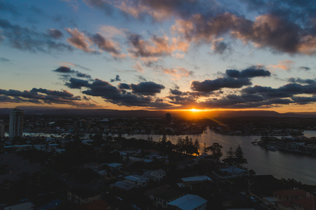 GOLD COAST, AUSTRALIA - January 16th, 2015: sun flare and tropical sunset over Surfers Paradise with mountain view