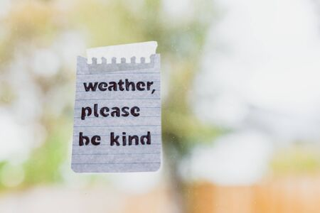 Foto de weather events and climate change conceptual still-life, Weather please be kind message with sticky tape on window glass with bokeh on stormy weather and grey sky over a backyard - Imagen libre de derechos