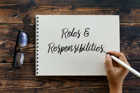 Top view of glasses and hand holding pen writing Roles and Responsibilities on notebook on wooden background.