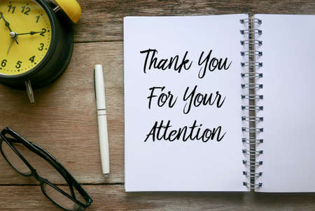 Photo pour Top view of clock,glasses,pen and notebook written with Thank You For Your Attention on wooden background. - image libre de droit