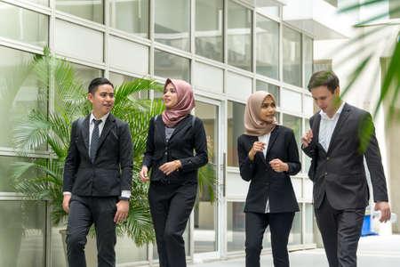 Foto de A group of young mixed Asian Executive at the corridor walking and talking to each other - Imagen libre de derechos