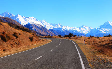 An empty road in New Zealand with snow-capped mountains on the background