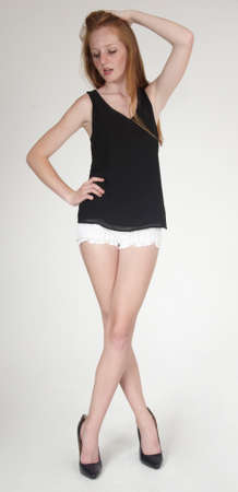 Photo for Red Head Teen Girl  in shorts and high heels - Royalty Free Image