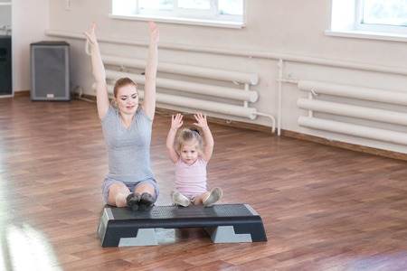 Photo for Pregnant woman with her first kid daughter doing gymnastics in living room. - Royalty Free Image