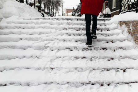 Photo for woman climbs the stairs in the snow - Royalty Free Image