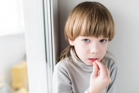 Photo pour Little blonde boy taking drugs and take vitamins - image libre de droit