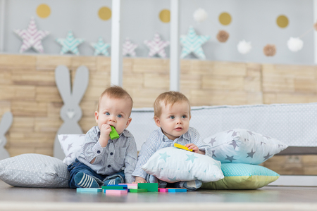 Photo pour Baby boy twins playing with the toy wooden cubes and dice - image libre de droit