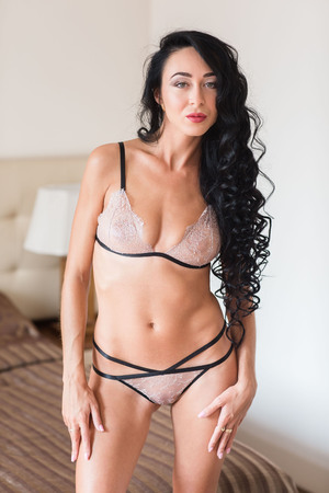Photo pour indoor glamour portrait of seductive young female in erotic pose wearing only lingerie - image libre de droit