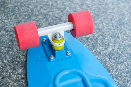 Back of blue plastic skate board. Red wheels.