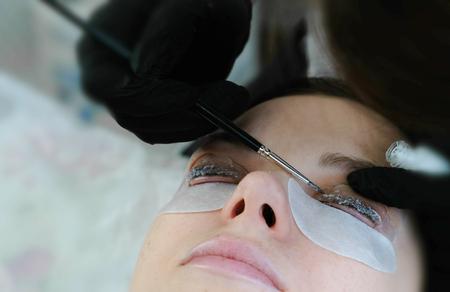 Foto de Beauty treatment. Beautician put a solution on curler eyelash curler with brush. lash lamination. - Imagen libre de derechos