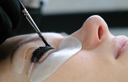 Foto de Beauty treatment. Cosmetologist puts black paint on the lashes. laminating eyelashes. Closeup face side view. - Imagen libre de derechos
