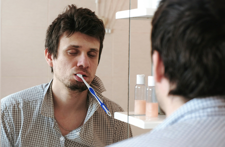 Tortured sleepy only waking man in front of the mirror with a toothbrush in his mouth.