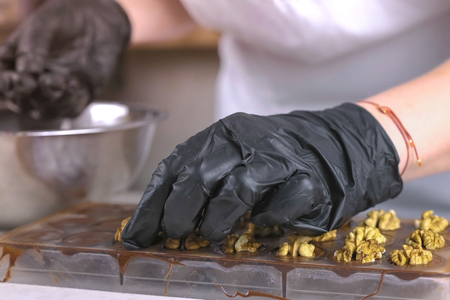 Bakers hands put the halves of walnuts on the chocolate candy in the forms.