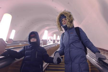 Foto de Mom and son in winter clothes are moving up the escalator in the subway tunnel. - Imagen libre de derechos