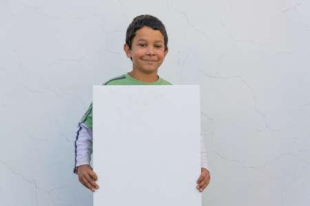 Smiling gypsy child boy holding white banner