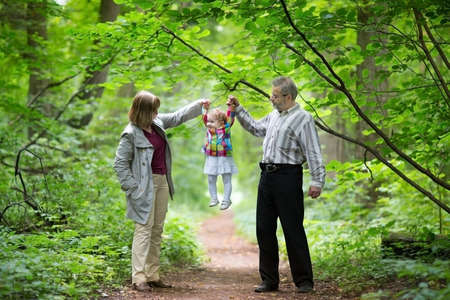 Photo pour Young grandparents playing with their baby granddaughter in an an autumn park  - image libre de droit