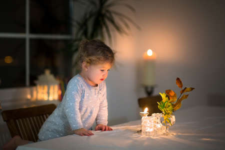 Portrait of a beautiful little girl watching candles in a dark dining room