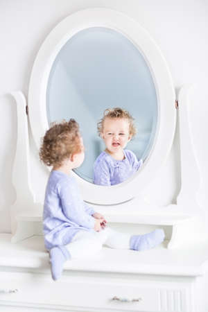 Adorable curly toddler girl making funny faces watching her reflection in a beautiful white mirror
