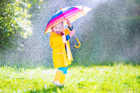Funny cute curly toddler girl wearing yellow waterproof coat and boots holding colorful umbrella playing in the garden by rain and sun weather on a warm autumn or sumemr dayの写真素材