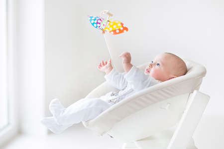 Cute Newborn Baby Boy Watching A Colorful Mobile Toy Sitting In A
