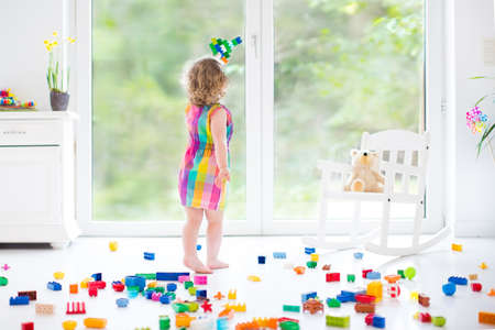 Photo for Cute laughing toddler girl playing with colorful blocks, building and airplane in a sunny bedroom with a big window   - Royalty Free Image