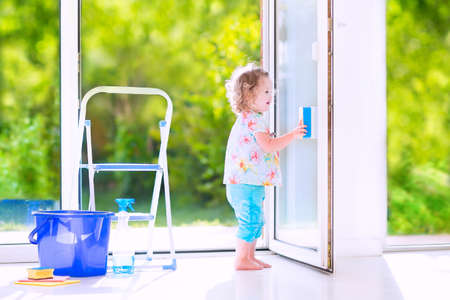 Cute laughing curly toddler girl washing a big window with a squeegee in beautiful white living room with door into the garden, standing on a ladder next to a blue bucket with water, detergent solution spray bottle and sponge