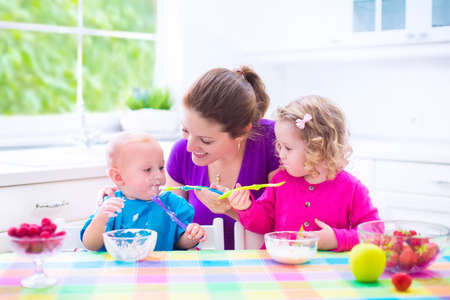 Photo pour Happy young family, mother with two children, adorable toddler girl and funny baby boy having healthy breakfast eating fruit and dairy, sitting in a white sunny kitchen with window - image libre de droit
