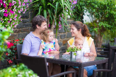 Photo for Happy young family, parents with two children, adorable little girl and a funny baby boy, eating lunch in a beautiful outdoor cafe with flowers in a city center on a warm summer day - Royalty Free Image