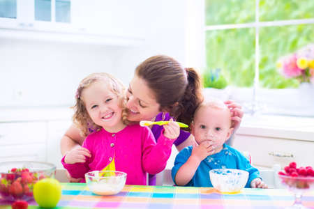 Photo pour Happy young family, mother with two children, adorable toddler girl and funny messy baby boy having healthy breakfast eating fruit and dairy, sitting in a white sunny kitchen with window - image libre de droit