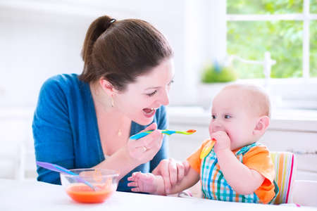 Young attractive mother feeding her cute baby son, giving him his first solid food, healthy vegetable pure from carrot with a plastic spoon sitting in a white sunny kitchen at a window