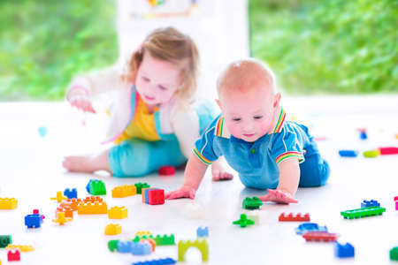 Photo for Adorable laughing toddler girl and a funny little baby boy, brother and sister, playing with colorful blocks sitting on a floor in a sunny bedroom with a big window  - Royalty Free Image
