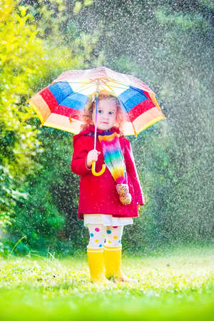 Funny cute curly toddler girl wearing red waterproof coat and yellow rubber boots holding colorful umbrella playing in the garden by rain and sun weather on a warm autumn or summer dayの写真素材