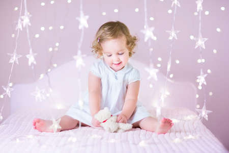 Photo pour Beautiful toddler girl with curly hair wearing a white dress playing with her bear toy sitting on a white bed in a pink bedroom between soft Christmas lights - image libre de droit